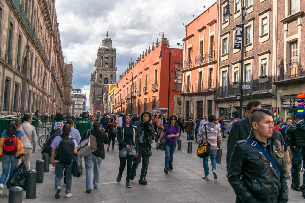 crowds of tourists on a colorful street, a common sight during a 3 day itinerary for mexico city