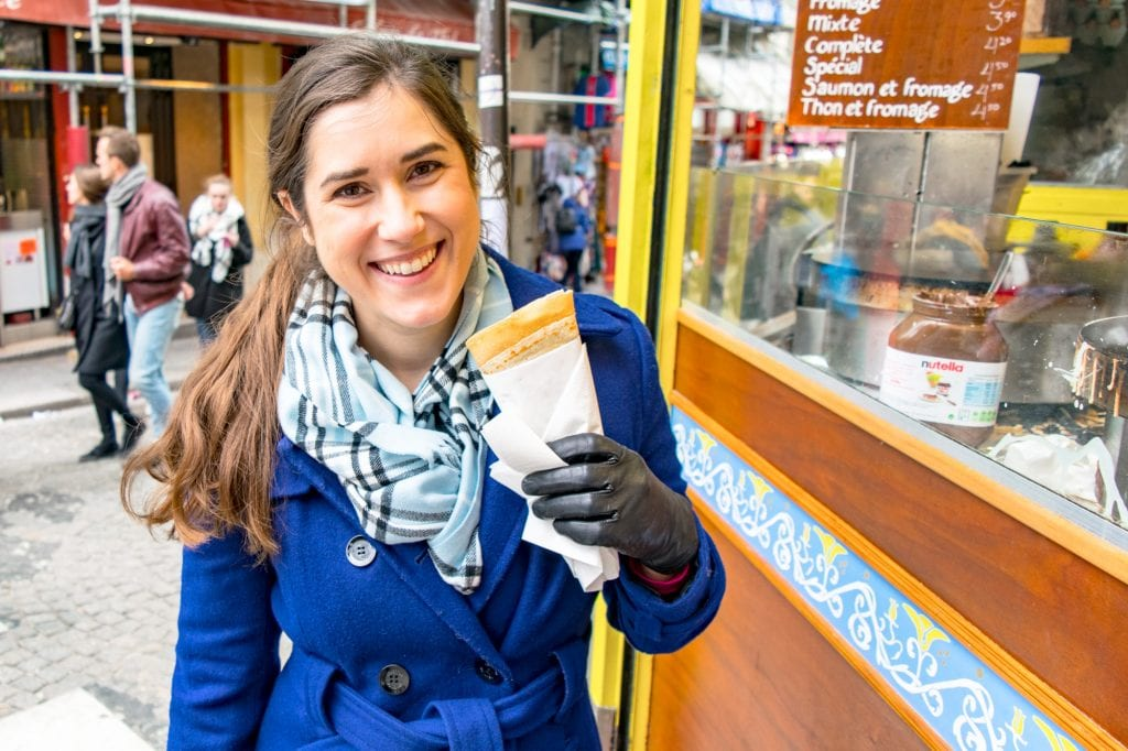 Kate Storm in a blue coat holding a crepe while sightseeing in Paris--any weekend trip to Paris definitely requires eating at least a couple of crepes!