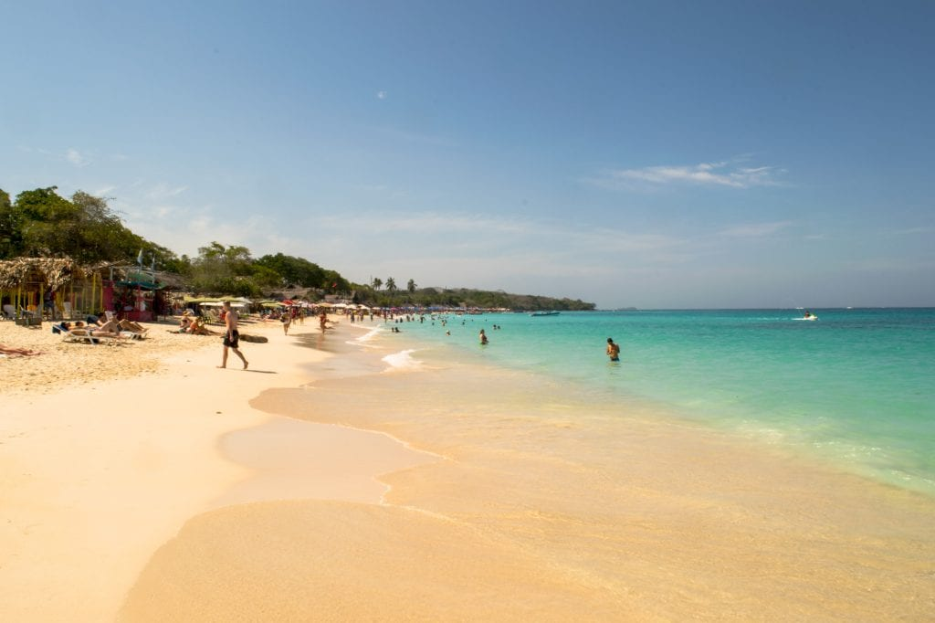Playa Blanca in Colombia as seen looking down the beach with the turquoise sea on the right and golden sand on the left