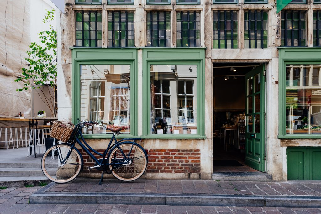historic building in ghent belgium with green trim and a bicycle parked in front