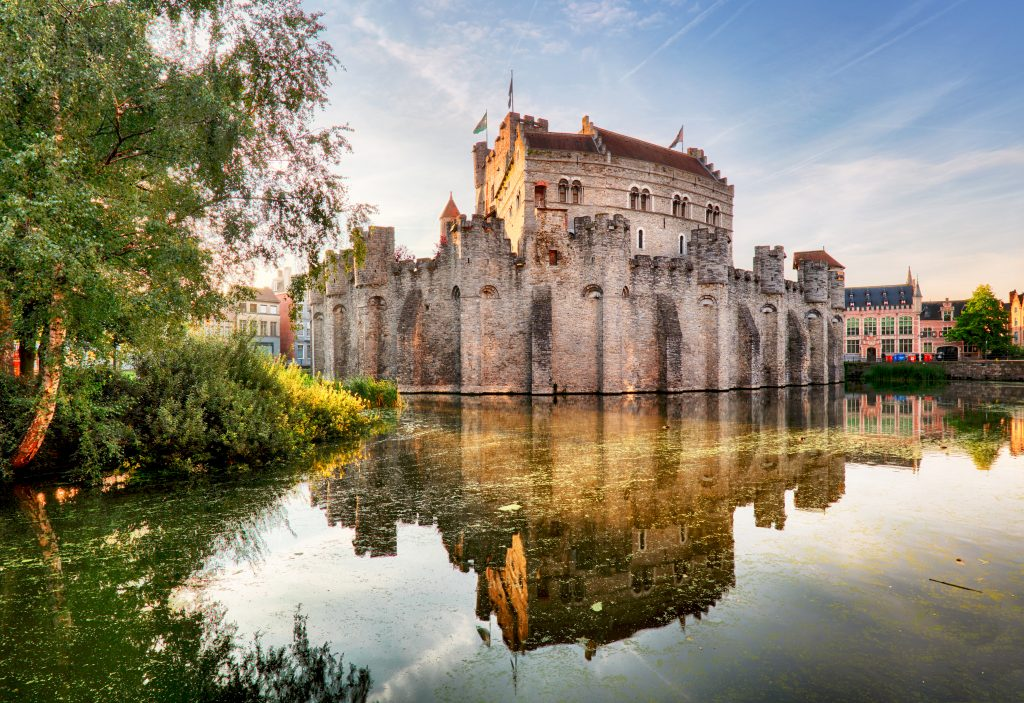gravensteen castle near sunset as seen from across the canal, one of the best places to visit in ghent belgium