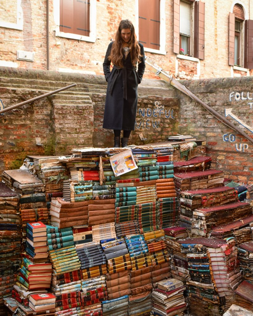 kate storm standing on top of a staircase of books at libreria acqua alta venice italy