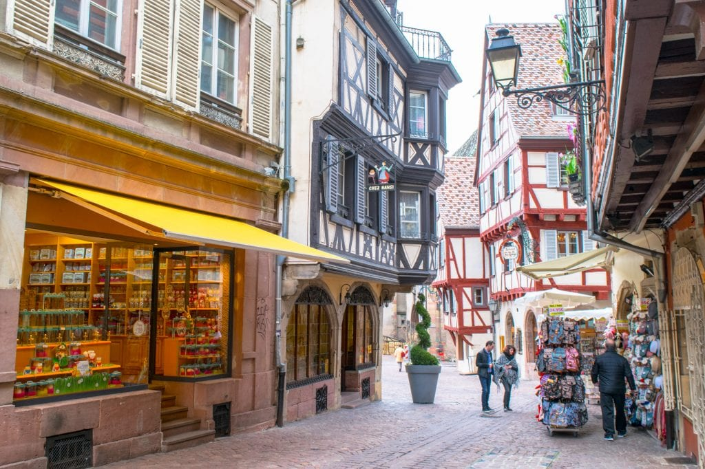 Small shopping street in Colmar France's Old Town with half-timbered houses on either side