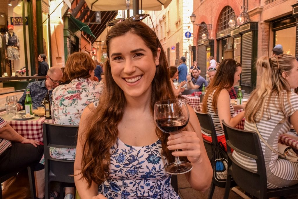 Woman drinking wine at restaurant in Bologna, Florence to Bologna Train