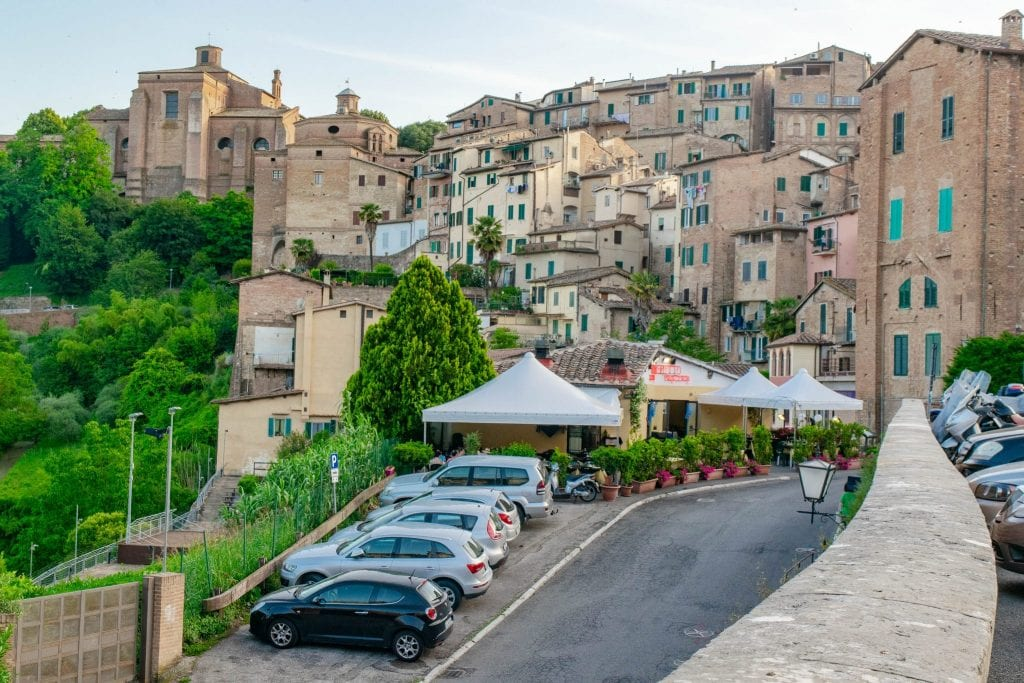 Cars parked outside of Siena Italy--parking outside of historical city centers is the norm when on a Tuscany road trip!