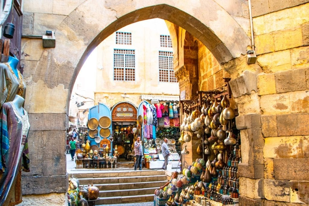 archway of egyptian bazaar with goods for sale on either side
