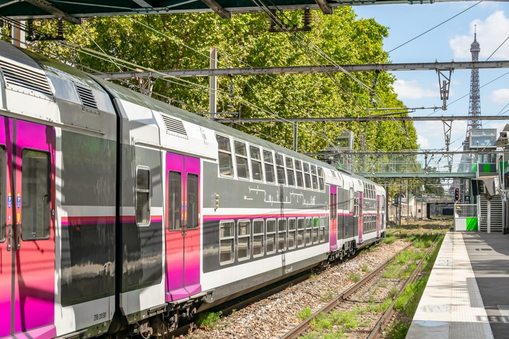 Photo of a pink and white train in a station in Paris. You can see the Eiffel Tower in the top right of the photo. If you follow this 3 day Paris itinerary, you might take this train to Versailles.