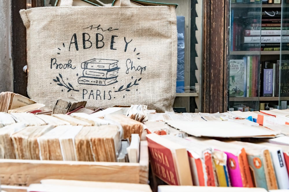"Photo from Abbey Bookshop in Paris. There are the tops of spines of books visible in the foreground and a tote bag that says ""Abbey Bookshop"" in the background."