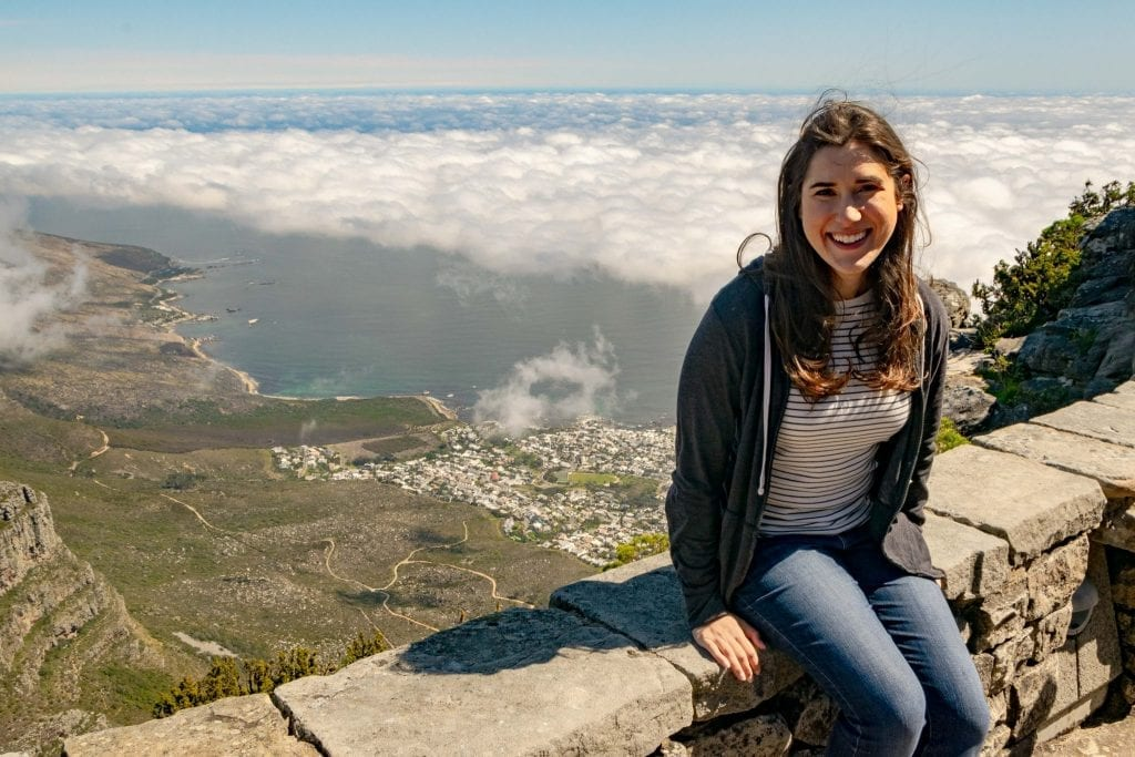 kate storm sitting over the clouds on table mountain cape town, one of the best stops itinerary south africa