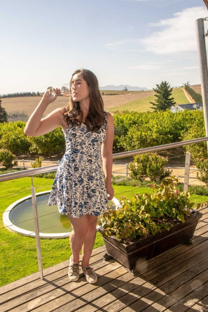 kate storm drinking a glass of wine at a vineyard in the cape winelands