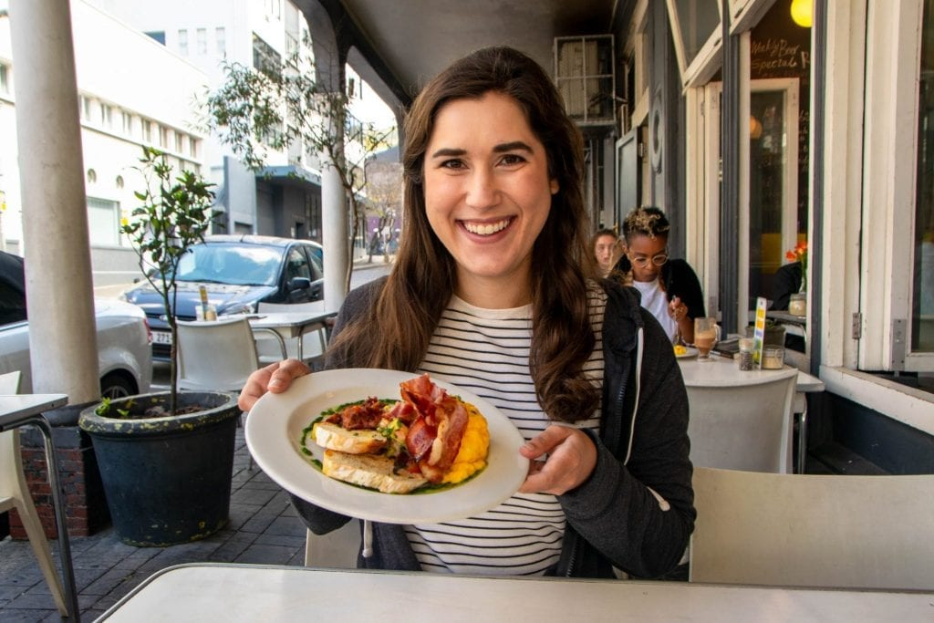 kate storm holding up a breakfast in cape town south africa itinerary