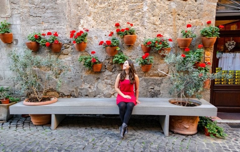 Kate sitting on a bench in Orvieto Italy. She's wearing a red dress, black tights, and black boots. There are red flowers in pots on the wall behind her.