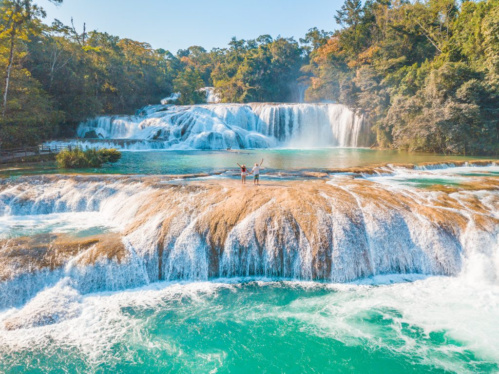 couple standing on agua azul in chiapas, one of the best mexico waterfalls