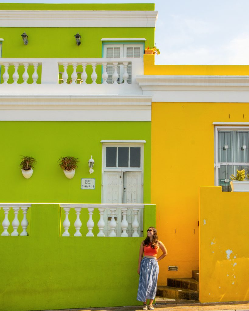 kate storm posing between a yellow and green building in bo kaap cape town