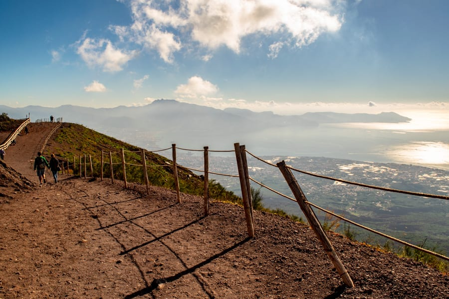 Photo of trail along the crater of Vesuvius, with distant view of Capri on the upper right. There's a crooked wooden hand rail.