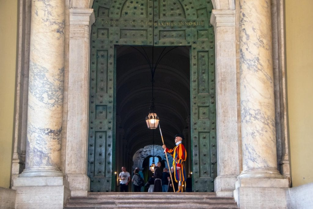 Vatican Guard standing in front of a large green door in Vatican City