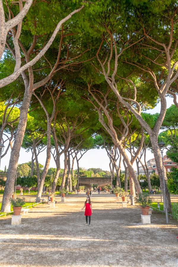 Kate Storm walking through Orange Garden in Rome Italy while wearing a red dress--a fun example of what to pack for Rome Italy