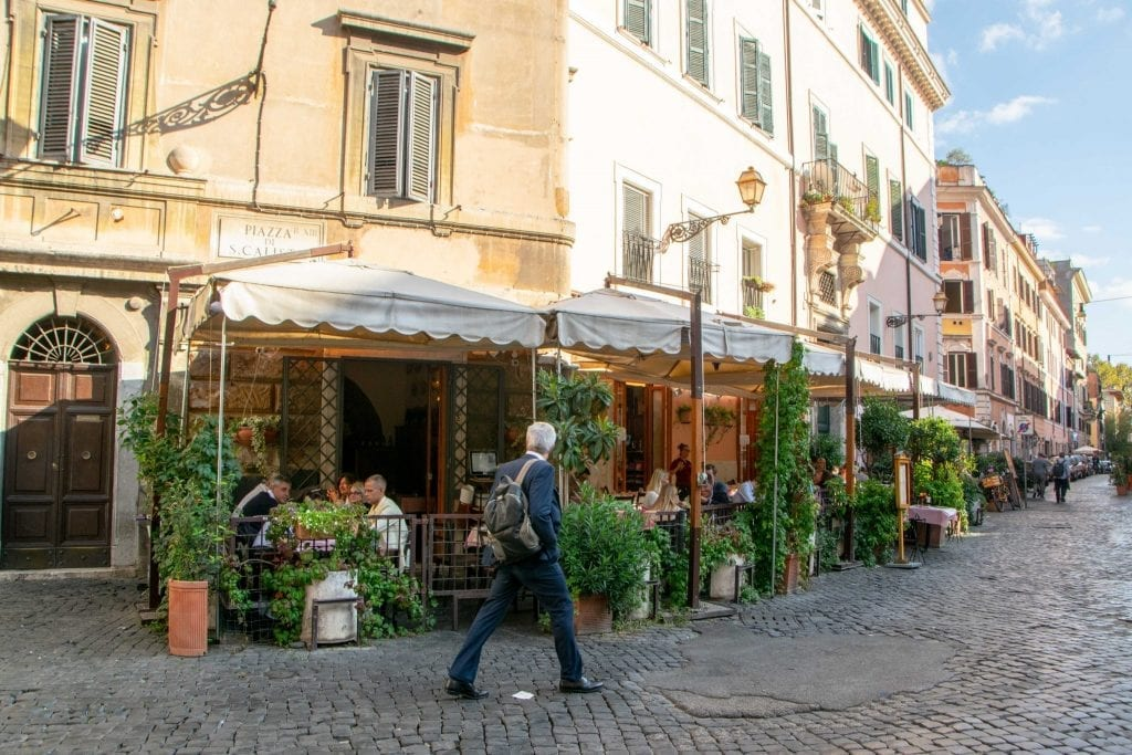 What to wear in Rome for men: man in Trastevere in front of restaurant