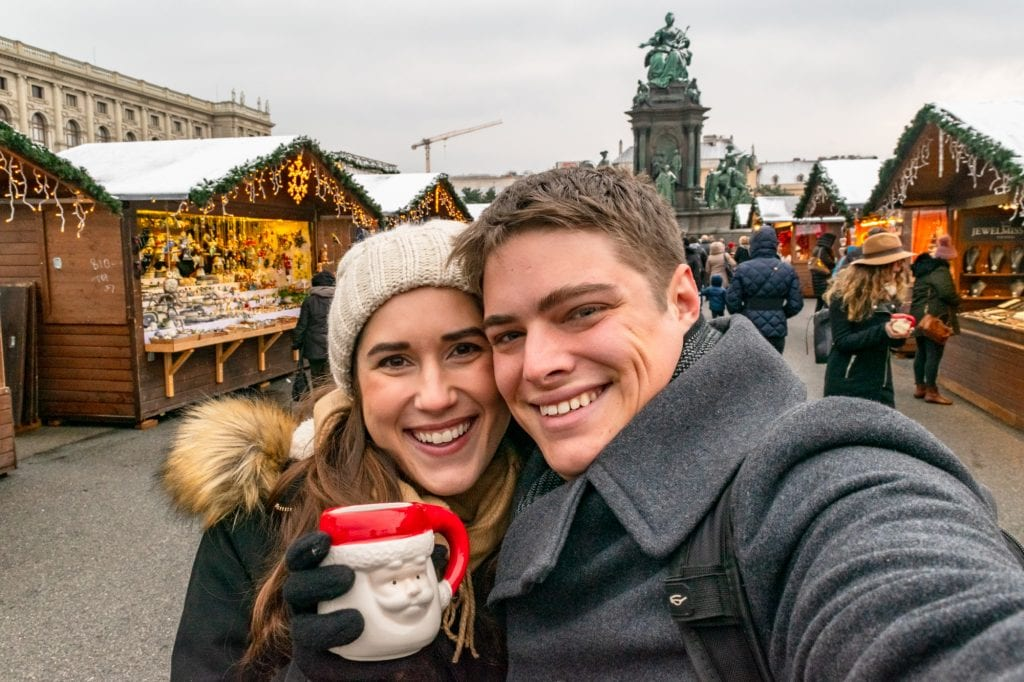 Kate and Jeremy in a Vienna Christmas market taking a selfie. Kate is holding up and red and white Santa mug.