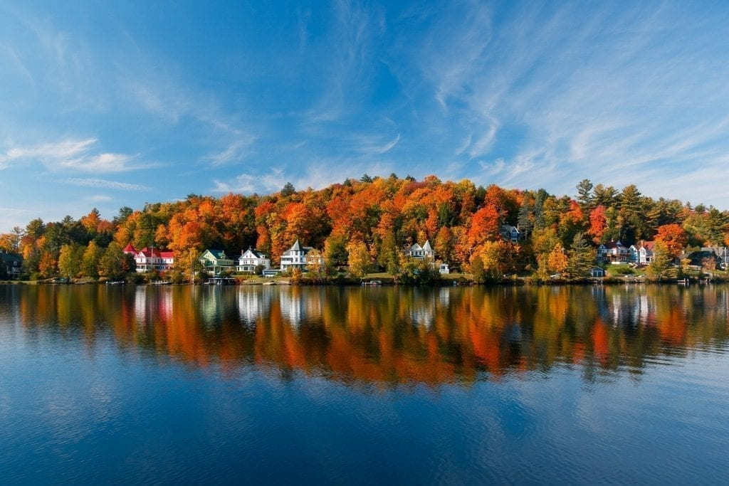 Saranac Lake, Adriondacks New York in the fall, with houses nestled against the lake shore, taken from across the water. Upstate NY in the fall in is one of the most romantic USA trips to take!