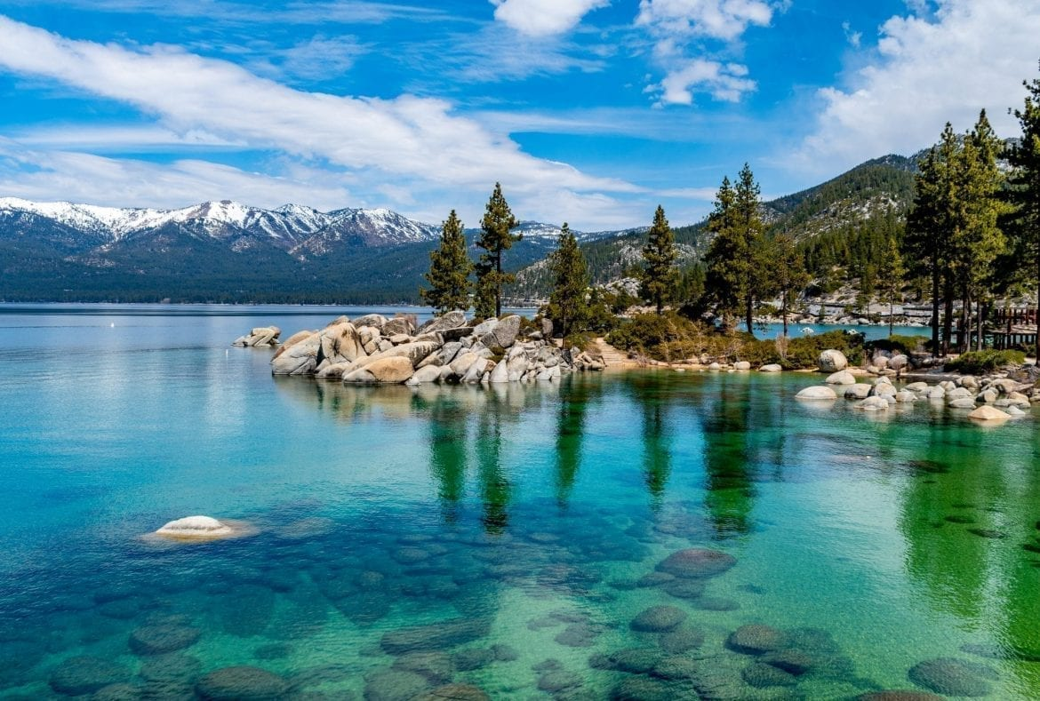 Clear water of Lake Tahoe California in summer with snowcapped mountains in the background--one of the best places to visit in the USA bucket list