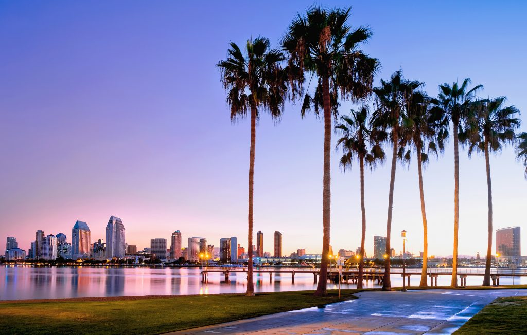 view of sunrise on coronado island california with palm trees in the foreground, one of the most romantic getaways in the us