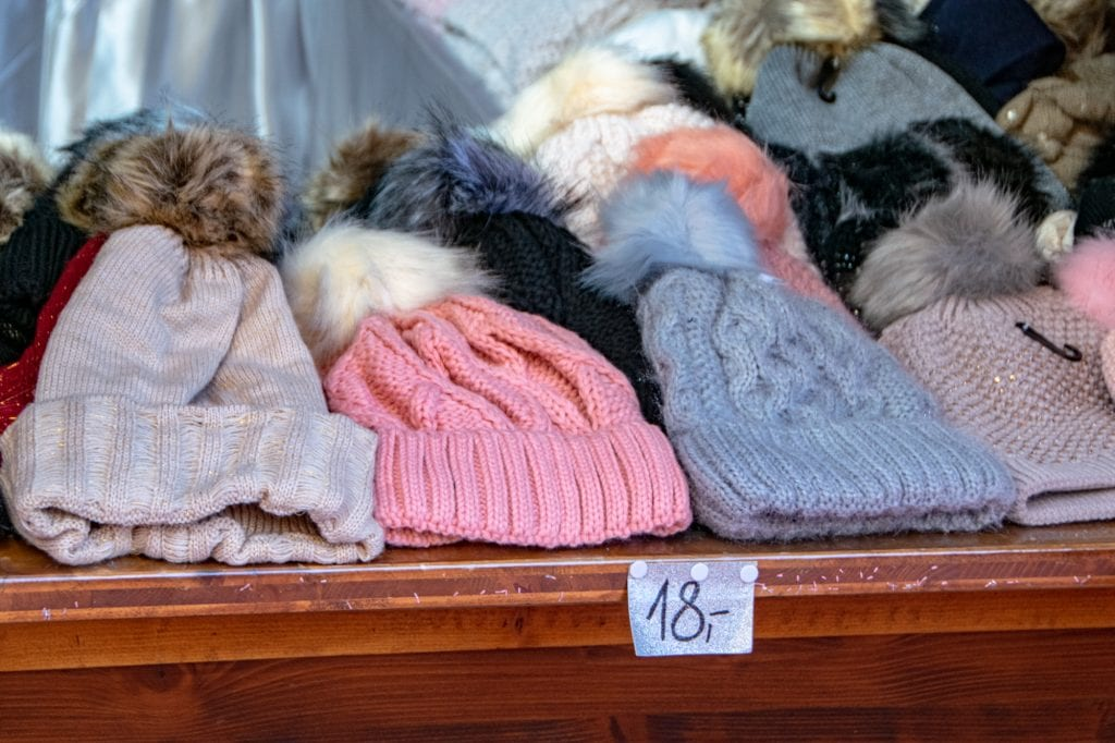 Pile of knit hats laying on a wooden table at a Christmas market in Innsbruck Austria--you'll be able to pick up plenty of souvenirs like this, so don't put too many accessories on your packing list for Europe winter!