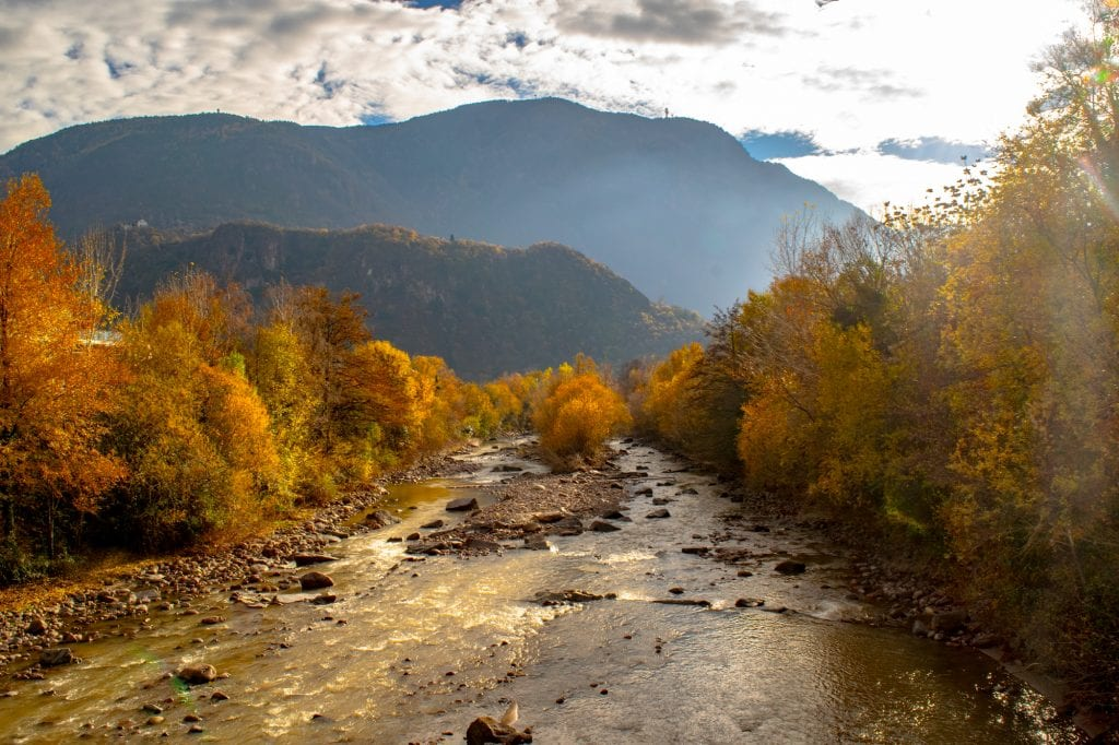 How to Use an Eurail Train Pass: photo of river surrounded by fall foliage in Bolzano.