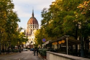 Photo of a street in Budapest lined by leafy green trees. Dome of Hungarian Parliament is in the distance.