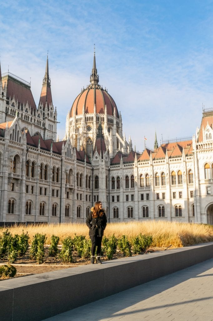 Woman in a black coat standing in front of Budapest Parliament in November.