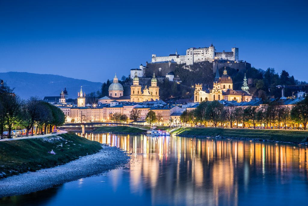 view of salzburg fortress at blue hour with the river in the foreground