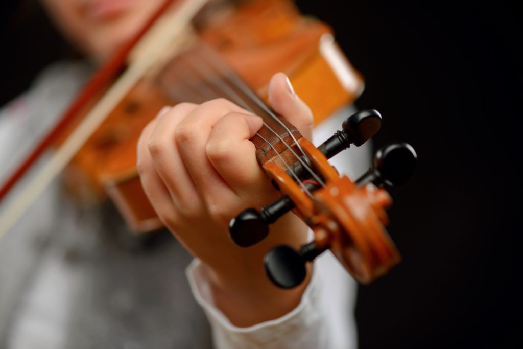 man playing a violin at a winter concert