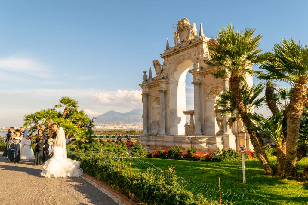 photo of a wedding taking place along the coast in naples, a beautiful italy proposal ideas