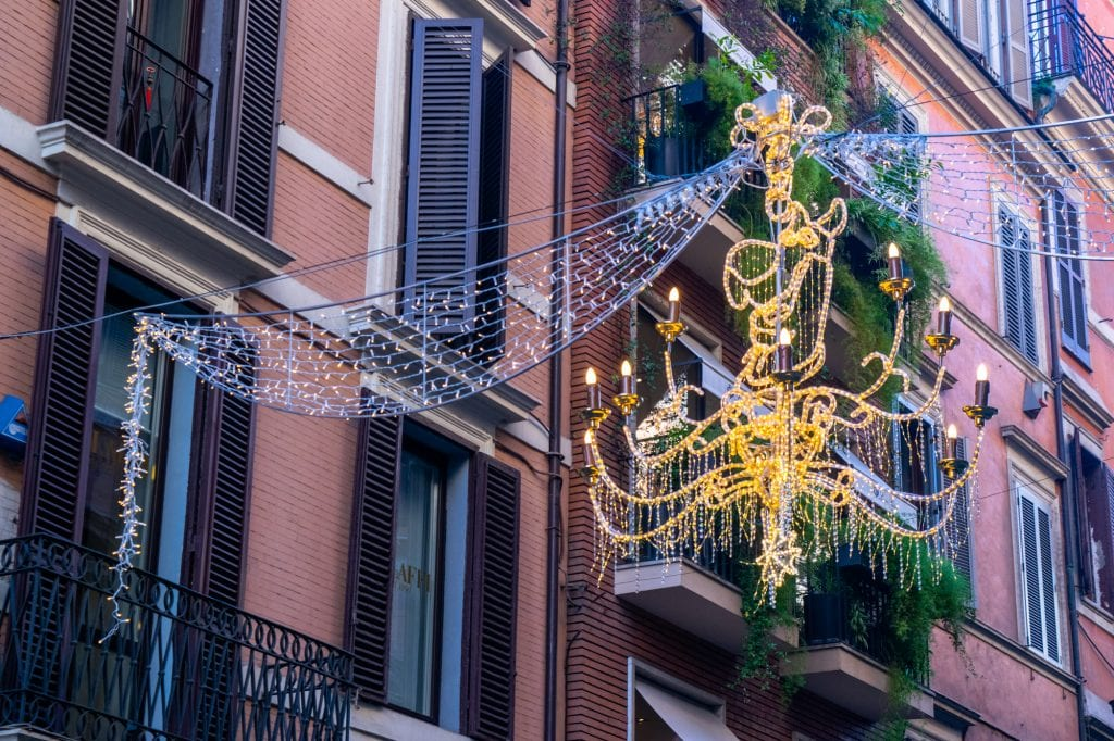 Christmas Lights Chandlier in front of pink Roman building: Rome in Winter
