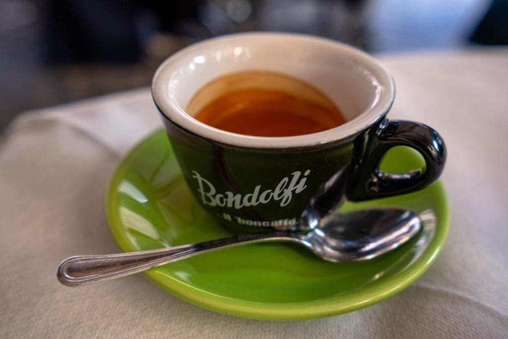 Shot of espresso close up in Rome on a green plate with a spoon resting on it--if you listen to any of these travel tips for Rome, be sure to remember to drink lots of espresso!