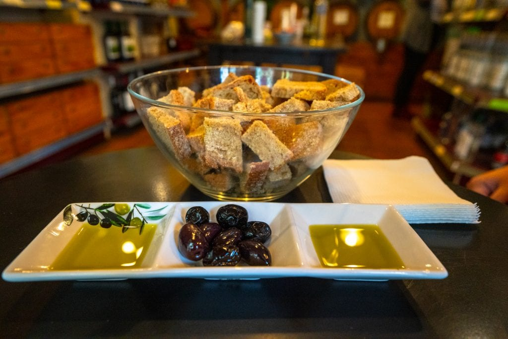 Olive oil, olives, and bread in a bowl served on Athens food tour