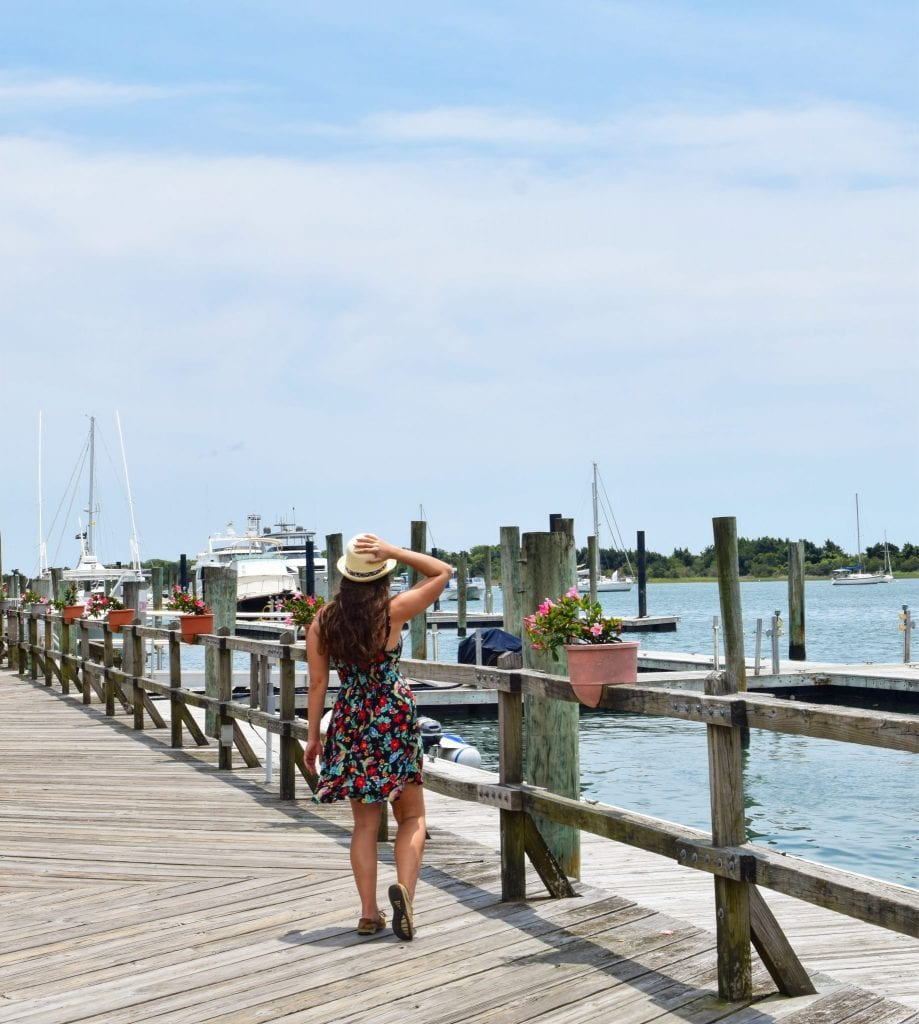 Kate Storm in a floral dress on a boardwalk, one of the best things to do in Beaufort NC, with sailboats in the background