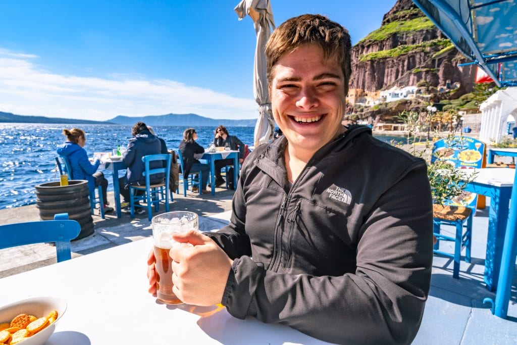 Man drinking a beer at Fira Old Port, 3 day Santorini itinerary