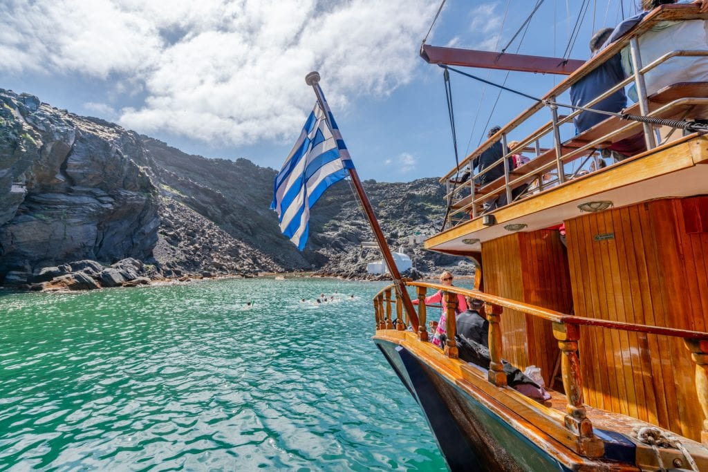 Tourist boat with Greek flag at volcano hot springs, 3 days in Santorini itinerary