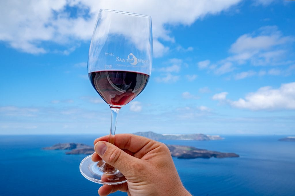 Glass of red wine being held up against sky, Honeymoon in Santorini