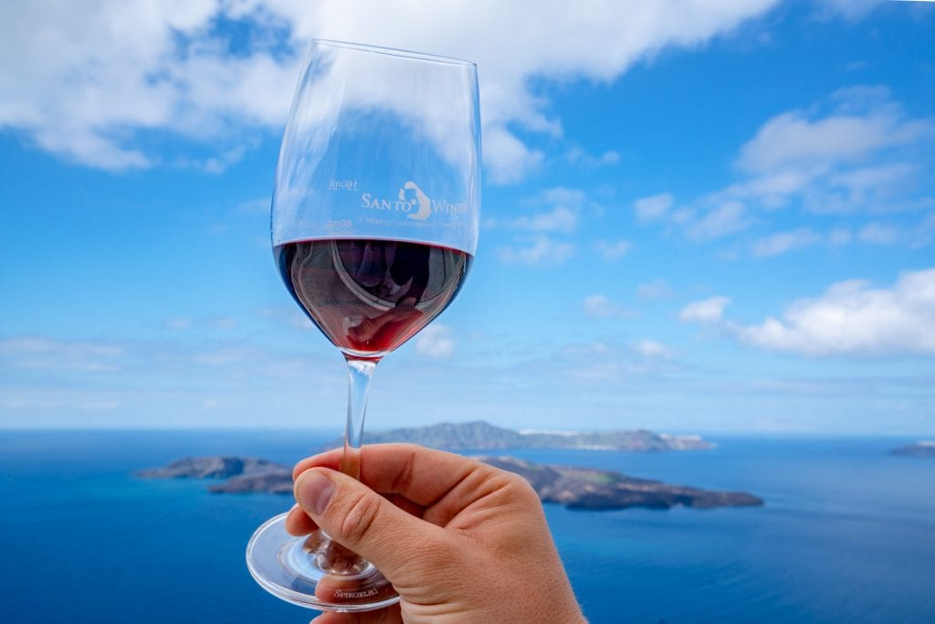 Glass of red wine being held up against sea, 3 day Santorini itinerary
