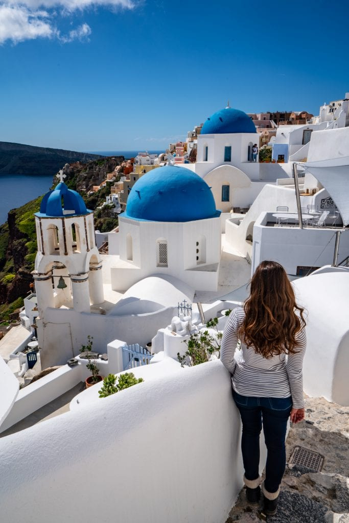 Kate Storm in a white shirt and blue jeans overlooking the blue domes of Oia in Santorini--this island is incredible and worth visiting as part of your 2 weeks in Europe!