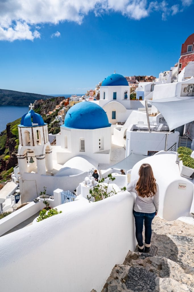 Girl standing in front of 3 blue domes on Santorini, Honeymoon in Santorini