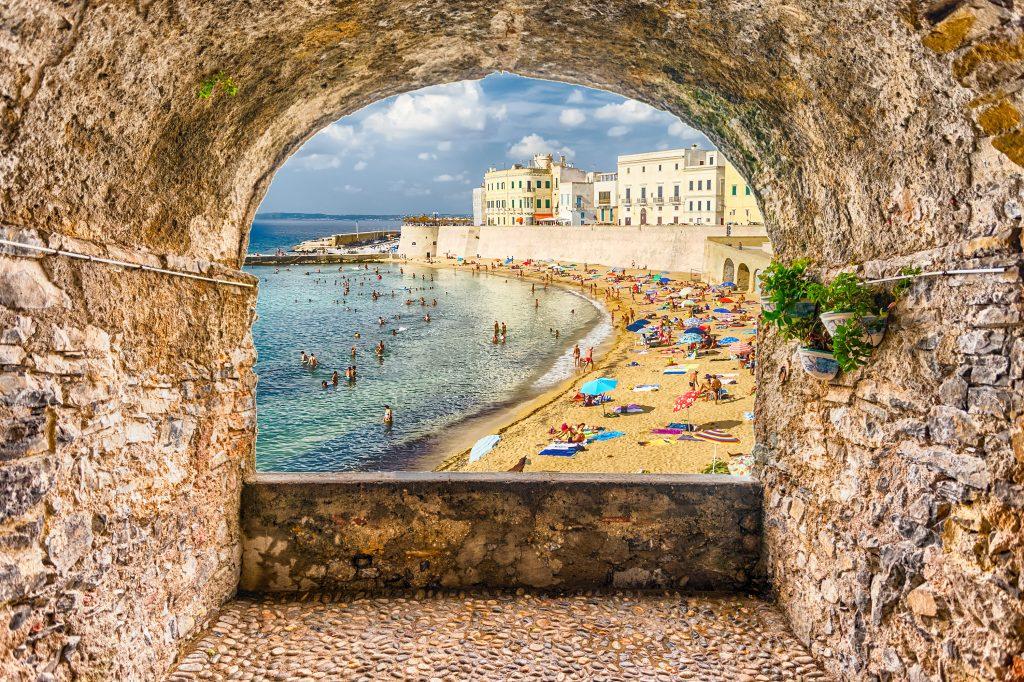 beach of gallipoli puglia as seen through a stone wall, one of the best italian coastal towns