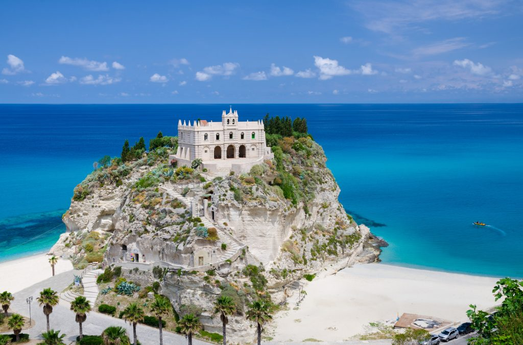 white castle of tropea italy sitting on an outcropping of rock with the sea in the background, one of the best seaside towns in italy