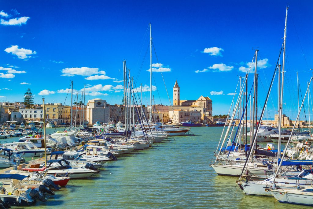 harbor of train puglia with sailboats in the foreground, one of the best italy coastal towns