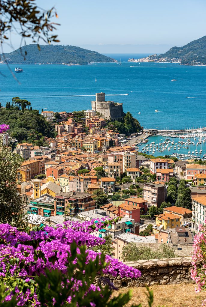 view of lerici italy from above with purple flowers in the foreground and the sea in the background