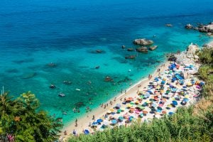 crowded white beach in italy surrounded by the water in tropea, one of the best beach towns in italy