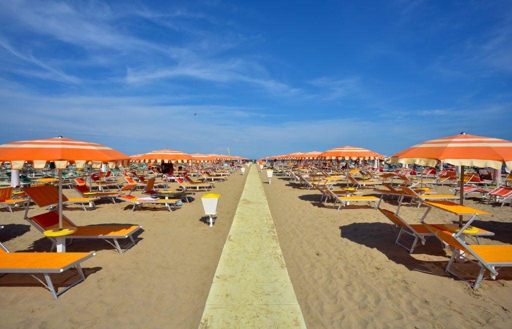 view of orange umbrellas set up in rimini, one of the best beaches in italy