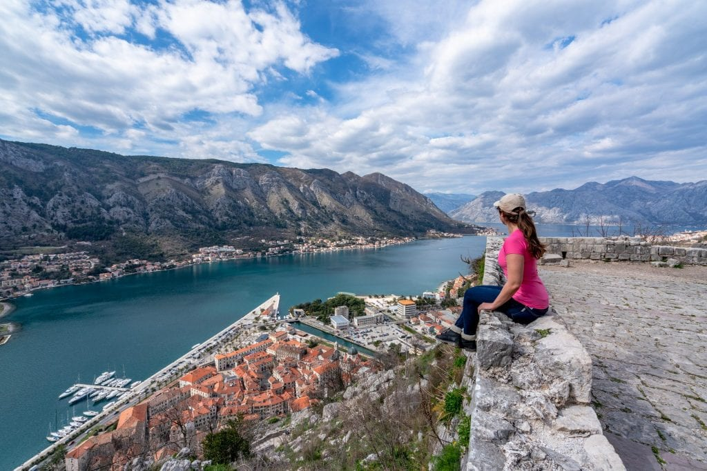 Kate Storm in a pink shirt climbing San Giovanni Fortress: Best Things to Do in Kotor Montenegro